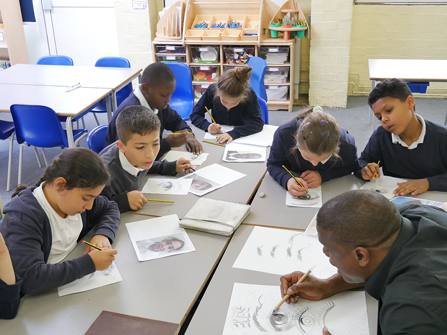 Adebanji sketching with pupils at Tiverton primary school